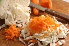 Cabbage and carrots. Cut cabbage and carrots on a wooden board Stock Photo