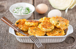 Cabbage patties. Healthy vegetarian cabbage patties with carrot and onion against the backdrop of sour cream sauce with herbs Royalty Free Stock Photo