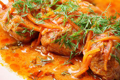 Cabbage rolls in tomato gravy on a white plate. Cabbage rolls in tomato gravy with carrots and fresh dill on a white plate. Close-up royalty free stock photos