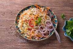 Cabbage salad with carrots, red pepper, onions, cilantro and spices. In a bright plate on a wooden table, selective focus. Delicious healthy food royalty free stock image