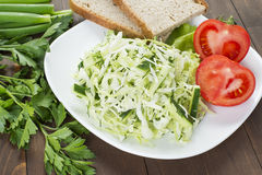 Cabbage salad with cucumber, tomatoes and herbs. Laid out on a white plate with bread Stock Photos