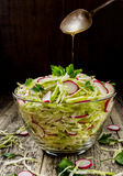 Cabbage salad with radish with shallow depth of field. Fresh vegetable salad from chopped cabbage and radish roses. On a dark background of old boards Royalty Free Stock Photo