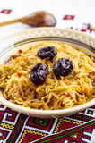 Cabbage stew with prunes. In a bowl with the Ukrainian ornament on the background of towel Stock Photography