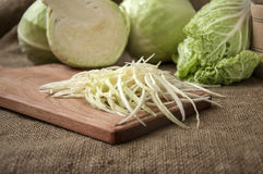 Cabbage on a wooden board on a background sacking, burlap Stock Images