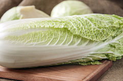 Cabbage on a wooden board on a background sacking, burlap Stock Photos