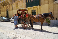 The cabby gives a tour to the tourists on the St Paul`s Square,. MDINA, MALTA - JULY 29, 2015:  The cabby gives a tour to the tourists sitting in the horse Royalty Free Stock Photography