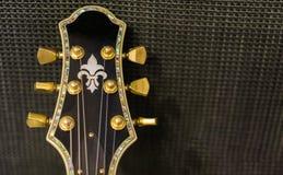 Cabeça bonita da guitarra com os botões giratórios dourados e o embutimento decorativo isolados em um fundo do amplificador da mú fotografia de stock