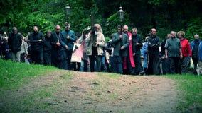 A cabeça cinzenta e o homem superior da barba levam a cruz como a procissão de Jesus Christ People filme