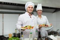 Cabeça-cozinheiros que cozinham na cozinha profissional imagens de stock royalty free