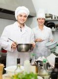 Cabeça-cozinheiros que cozinham na cozinha profissional imagem de stock