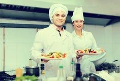 Cabeça-cozinheiros que cozinham na cozinha profissional imagens de stock