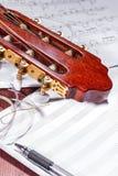 A cabeça da guitarra clássica, das notas, de cordas novas e de uma pena em uma tabela de madeira foto de stock