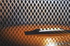 Cabeça da guitarra com os afinadores dourados na frente do amplificador poderoso da guitarra do vintage com a grade brilhante do  imagem de stock