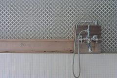 A cabeça de chuveiro do estilo do vintage ajustou-se na prateleira de madeira acima sobre a banheira no banheiro exterior imagens de stock