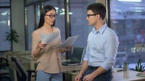 Cabeça de departamento asiática satisfeita com o informe anual de seu assistente masculino vídeos de arquivo