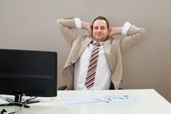 Cabeça de With Hands Behind do homem de negócios no escritório imagem de stock royalty free