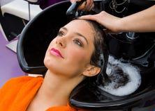 Cabeça de lavagem da mulher do estilista de cabelo Imagens de Stock