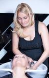 Cabeça de lavagem da mulher do estilista no salão de beleza de cabelo Fotos de Stock