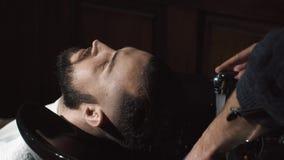 Cabeça de lavagem do homem do barbeiro no barbeiro vídeos de arquivo