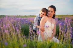A cabeça de uma criança loving encontra-se no ombro de uma mãe bonita Fotografia de Stock