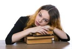 A cabeça de uma menina encontra-se em uma pilha dos livros isolados Fotos de Stock Royalty Free