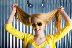 Cabeça disparada da mulher loura brincalhão em mordidas amarelas do eyewear sua língua fotos de stock royalty free