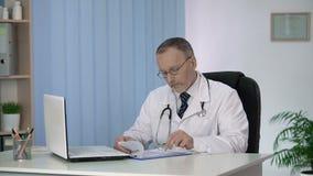 Cabeça do departamento terapêutico que termina seu dia útil, enchendo-se em formulários médicos vídeos de arquivo