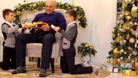 A cabeça do pai de família e os filhos dão-se presentes e sorrisos na sala de visitas com chaminé e a árvore de Natal alta video estoque