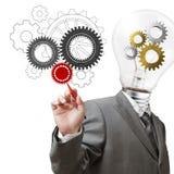 A cabeça e as rodas denteadas da ampola do homem de negócios desenham as engrenagens Foto de Stock Royalty Free