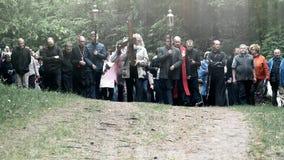 A cabeça e o ancião cinzentos da barba levam a cruz como a procissão dos povos de Jesus Christ video estoque