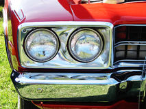 A cabeça ilumina o amortecedor do cromo de um carro vermelho imagens de stock royalty free