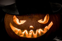 Cabeça má da abóbora de Dia das Bruxas no chapéu em um fundo escuro Fotos de Stock Royalty Free