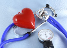 A cabeça médica do estetoscópio e o coração vermelho do brinquedo que encontram-se no cardiograma fazem um mapa do close up ajuda Fotos de Stock Royalty Free