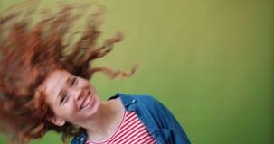 Cabeça movente do adolescente atrativo que acena o cabelo encaracolado no fundo verde vídeos de arquivo