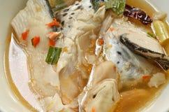 Cabeça picante dos peixes dos salmões e cogumelo de palha na sopa de Tom Yum na bacia imagens de stock