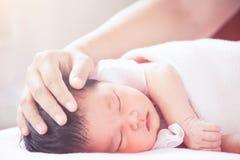 Cabeça recém-nascida asiática tocante do bebê da mão da mãe Imagem de Stock