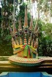 7 cabeças da serpente esculpiram o puppet& x27; bacia da cara da maxila de s Atrás de uma árvore natural Foto de Stock