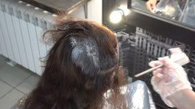 Cabeleireiro da mulher que faz a menina do procedimento da coloração de cabelo na barbearia Fim acima Vista traseira 4K filme