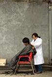 Cabeleireiro da mulher que trabalha com um homem do cliente nas ruas de fotografia de stock
