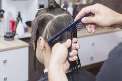 Cabeleireiro do estilista na barbearia que faz o close up do corte de cabelo Foto de Stock