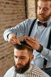 Cabeleireiro dos homens Barber Doing Haircut In Barbershop imagem de stock royalty free
