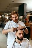 Cabeleireiro dos homens Homem Barber Doing Hairstyle In Barbershop foto de stock