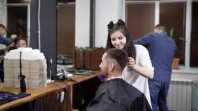 Cabeleireiro fêmea alegre no barbeiro que faz o selfie com o cliente masculino que senta-se na cadeira coberta com o protetor filme
