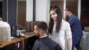 Cabeleireiro fêmea no trabalho Cliente masculino que sentam-se na cadeira, e o outro barbeiro e cliente no fundo Cena em vídeos de arquivo