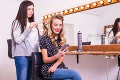 Cabeleireiro fêmea que aplica o straightener do cabelo para o cabelo longo da jovem mulher de sorriso que usa o smartphone Imagem de Stock