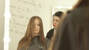 Cabeleireiro fêmea que penteia o cabelo longo com a escova de cabelo durante o corte no salão de beleza do cabeleireiro Feche aci filme