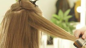 Cabeleireiro fêmea que usa tenazes de brasa e pente do cabelo para o cabelo que endireita no salão de beleza Feche acima do endir video estoque