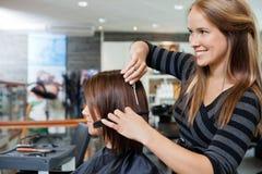 Cabeleireiro Giving um corte de cabelo à mulher imagens de stock royalty free