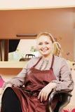 Cabeleireiro de sorriso na cadeira Fotos de Stock Royalty Free