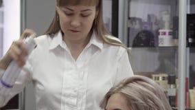Cabeleireiro Makes Professional Styling da mulher com um pulverizador video estoque